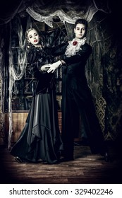 Beautiful man and woman vampires dressed in medieval clothing dancing in a room of the old abandoned castle. Halloween.