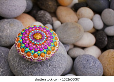 Beautiful mandala hand painted on a sea stone, with pebbles