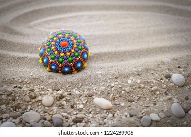 Beautiful mandala rock on sand