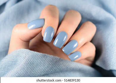 Beautiful manicure. Nail polish being applied to hand, polish is a blue color. Blue background closeup.
