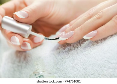 Beautiful manicure nails paint. Woman in nail salon applying manicure.Close up of nails varnish.