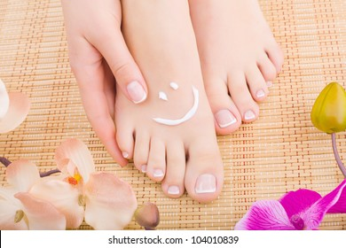 Beautiful manicured feet with pedicures and flowers. Close-up