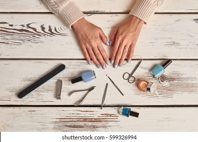 Beautiful manicured woman's nails with blue nail polish and tools. Nail salon. Still life of manicure accessories.