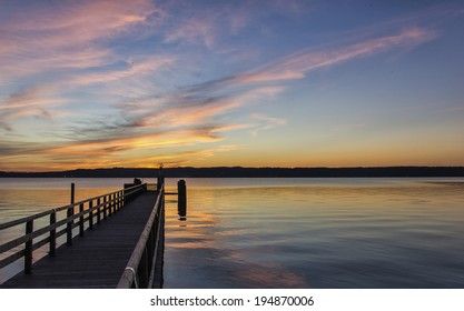 Beautiful marine sunset over a pier or jetty tinting the clouds a delicate pink and gold above a tranquil ocean