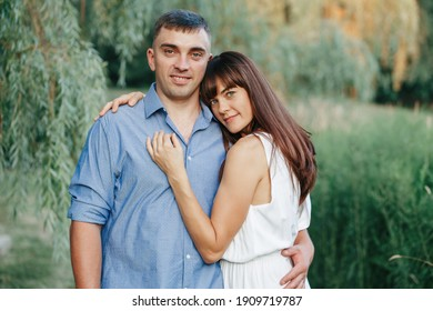 Beautiful married couple man woman in love. Husband and wife hugging in park on summer day at sunset. Togetherness and happiness. Authentic real people family outdoor.