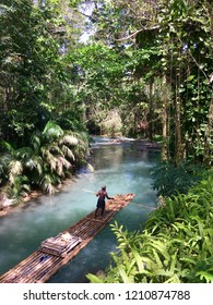 Beautiful Martha Brae river in Jamaica, man rafting on the blue river
