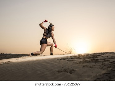 Beautiful martial arts female wearing black short tights and top showing midsection  as she performs a technique while holding two escrima sticks in the desert at sunrise or sunset