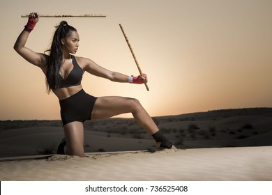 Beautiful martial arts female wearing black short tights and top showing midsection and long legs as she performs a technique while holding two escrima sticks in the desert at sunrise or sunset