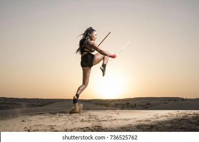 Beautiful martial arts female wearing black short tights and top showing midsection and long legs performs a jumping or flying  knee strick while holding two escrima sticks in the desert at sunrise