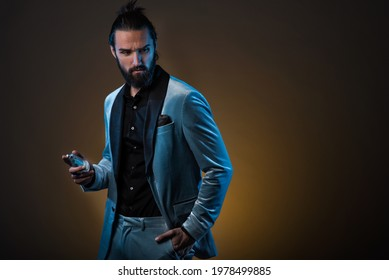 Beautiful masculine bearded young man holding a bottle of fragrance. Masculine perfume, bearded man in a suit. - Shutterstock ID 1978499885