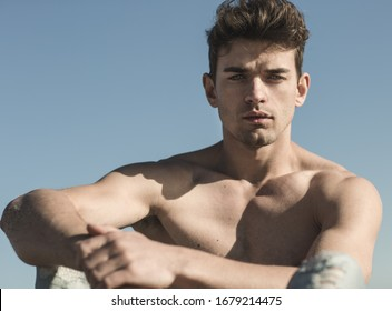 Beautiful masculine portrait of handsome topless male model outdoors.