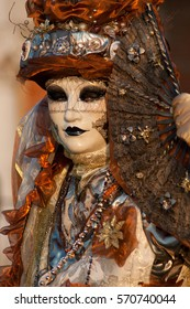 Beautiful mask in a red gold costume at carnival in Venice
