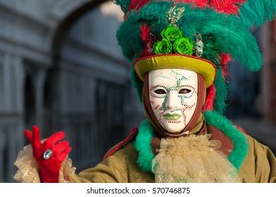 Beautiful mask in a red and green costume at carnival in Venice