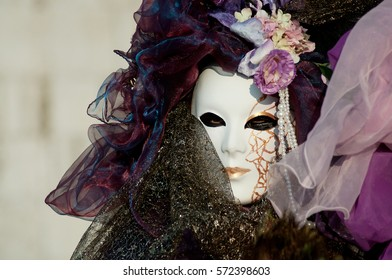 Beautiful mask in white and lilac costume at the Venice Carnival