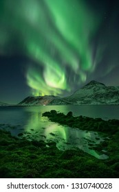 Beautiful massive northern lights (aurora borealis) over a fjord in Arctic Norway