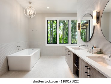 Beautiful master bathroom in new luxury home. Includes double vanity, bathtub, pendant light fixture, circular mirrors, tile floor, and view of trees.