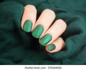 Beautiful matt nail polish in hand, close-up, green nail art manicure