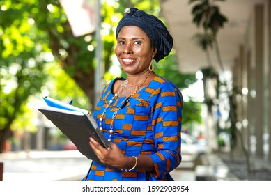 beautiful mature african businesswoman in traditional outfit standing outdoors holding a document and looking at camera smiling.