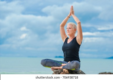 Beautiful mature aged woman doing yoga on a desert tropical beach.