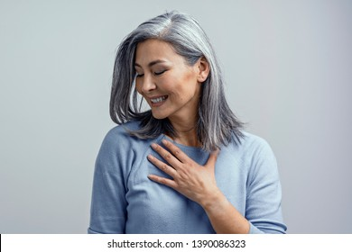 Beautiful Mature Asian Grey-Haired Woman Touches her Chest Gratefully and Smiles Coquettishly in Excitement. She is Half-Turned to Camera. Tonned Studio Shot.
