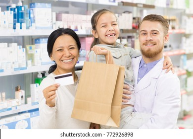 Beautiful mature Asian woman smiling joyfully holding her credit card posing with her little daughter and helpful pharmacist at the local drugstore shopping buying banking debit money affordable