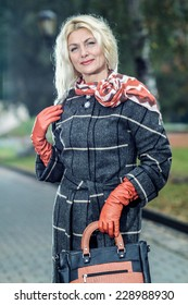 Beautiful mature blonde in checkered coat posing in the park. Portrait of a senior woman outdoors.