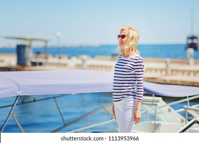 Beautiful mature blonde in a yacht club / Mature woman with a striped T-shirt at the sea / copy space