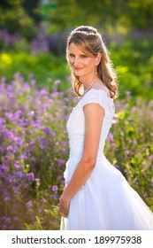 Beautiful mature bride in white wedding dress in a Spring field filled with lavender flowers.