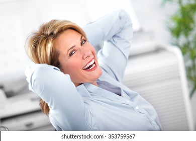 Beautiful mature business woman relaxing in modern office.