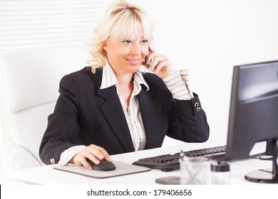 Beautiful mature Business woman talking on mobile phone at workplace.