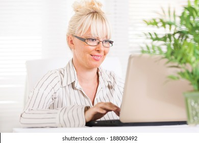 Beautiful mature Business woman working at laptop in the office