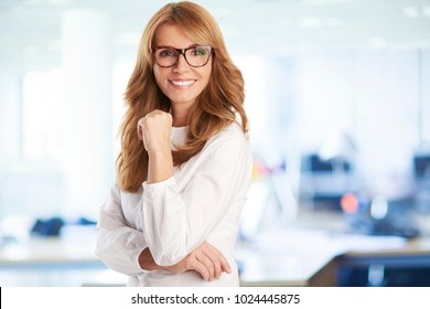 A beautiful mature businesswoman with toothy smile standing at the office with arms crossed.