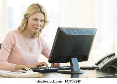 Beautiful mature businesswoman using computer in office