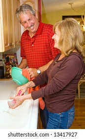 Beautiful mature couple cleaning the dishes together.