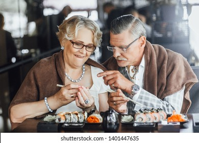 Beautiful mature couple eating sushi in cafe ,summer terrace,nice day,Sticks for sushi,teste