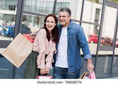beautiful mature couple embracing with shopping bags