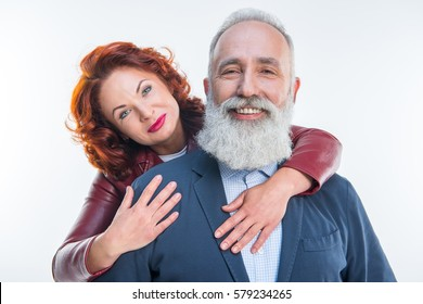 Beautiful mature couple hugging and smiling at camera isolated on white
