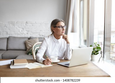 Beautiful mature female psychologist in eyewear and white blouse making notes in copybook, sitting at desk in front of open laptop computer and looking through window with thoughtful expression