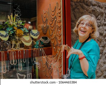 Beautiful mature happy tourist woman with old video camera on her neck travelling in Palma de Majorca stays smiling at jewelry show-window shop