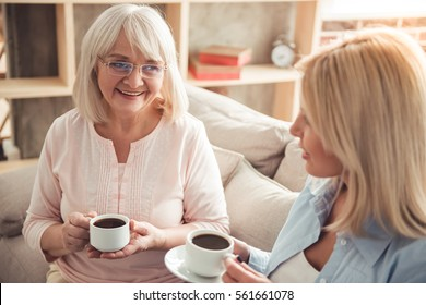 Beautiful mature mother and her adult daughter are drinking coffee, talking and smiling while sitting on couch at home