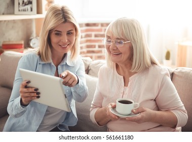 Beautiful mature mother and her adult daughter are drinking coffee, using a digital tablet and smiling while sitting on couch at home