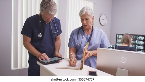 Beautiful mature nurse writing notes in patient file with male colleague