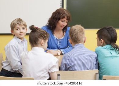 beautiful mature primary school teacher and four students read the book. Cute caucasian boy looks at the camera and smiling. Horizontal color image.