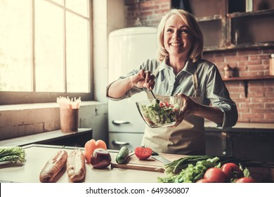 Beautiful mature woman in apron is mixing salad and smiling while cooking in kitchen