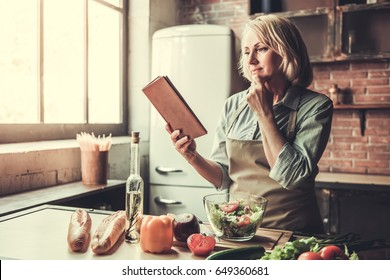 Beautiful mature woman in apron is reading a book with recipes while cooking in kitchen