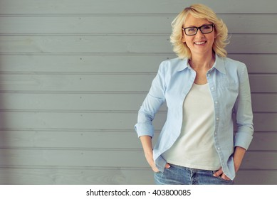 Beautiful mature woman in casual clothes and eyeglasses is looking at camera and smiling, standing against gray background