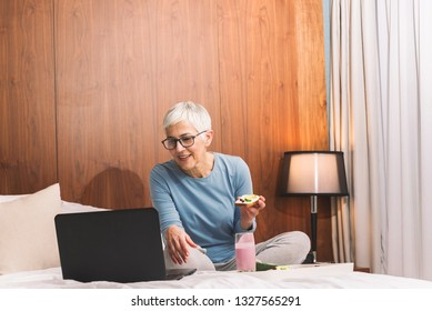 Beautiful mature woman chilling at home by her laptop, Weekend vibes and free time concept