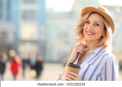 Beautiful mature woman with cup of coffee outdoors