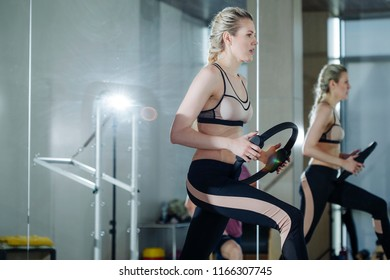 beautiful mature woman exercesfully performs the exercises of pilates in the fitness room holding  sports projectile