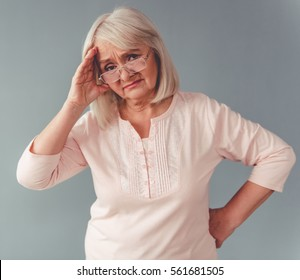 Beautiful mature woman in eyeglasses is touching her head having a headache, on gray background
